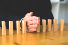 Business hand stops domino continuous overturned meaning that hindered business failure. Stop over this business failure concept.  royalty free stock image