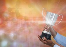 Business hand with trophy against a gold background and flares. Digital composite of business hand with trophy against a gold back ground and flares Stock Images