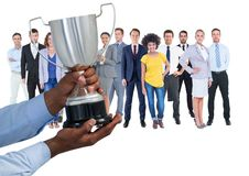 business hand with trophy in front of the workers of the company royalty free stock photos