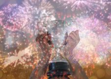 Business hand with trophy, gold background and fireworks. Digital composite of business hand with trophy, gold background and fireworks Royalty Free Stock Photos