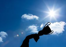 business hand  with trophy shade in the sky Royalty Free Stock Photography