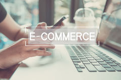 Business hand typing on a laptop keyboard with E-Commerce. stock photography