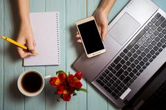 Business hand woman using computer and writing on blank notebook with telephone. Modern white office desk table with laptop, cup of coffee and flowers. Top royalty free stock photo