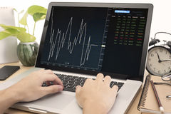 Business hand working on computer notebook with Finance Trading stock image