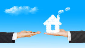 Business Hands with money and house from clouds. On blue sky background, concept for family and Estate concept royalty free stock photography
