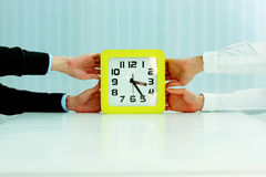 Business hands pulling clocks Royalty Free Stock Images