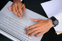 Business Hands at Work on a Sleek Laptop. Closeup of a businessman's hands typing on a sleek silver laptop with a gold pen in one hand Stock Photo