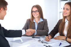 Business handshak  sitting at the desk on office background, copy space area at the left upper corner Stock Image