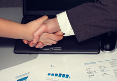 Business handshake. Woman and man's handshake against graphs and a grey  notebook Royalty Free Stock Images