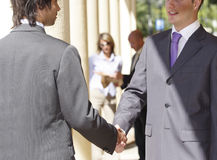 Business handshake. Two business men shaking hands, outside, people in the background Stock Images