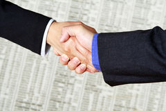 Business handshake. A handshake between two businessmen over financial figures Stock Photo
