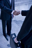 Business handshake. Two businessmen standing shaking hands on steps Stock Photos