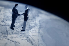 Business handshake. On a globe royalty free stock images