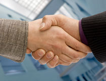 Business handshake. Man and woman business handshake with corporate background stock images