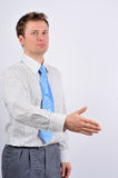 Business handshake. A trendy European businessman with a blue tie and shirt Royalty Free Stock Photos