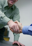 Business Handshake. Two businessmen give a handshake over a business deal in the office Stock Images