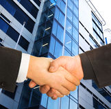 A business handshake. A business handshake in front of a building royalty free stock images