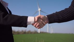 Business handshake against wind turbines. Business handshake of man and woman against wind turbines on sunny day stock footage