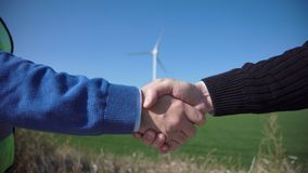 Business handshake against wind turbines. On sunny day stock video