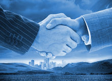 Business handshake on background of buildings and landscape. Close up of business people handshaking on background of buildings and landscape Stock Photo