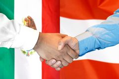 Handshake on Mexico and Austria flag background. Business handshake on the background of two flags. Men handshake on the background of the Mexico and Austria royalty free stock image