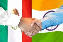 Handshake on Mexico and India flag background. Business handshake on the background of two flags. Men handshake on the background of the Mexico and India flag stock photography