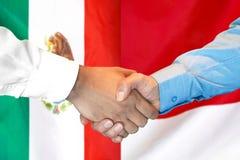 Handshake on Mexico and Monaco flag background. Business handshake on the background of two flags. Men handshake on the background of the Mexico and Monaco flag royalty free stock image