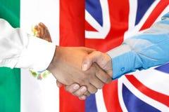 Handshake on Mexico and UK flag background. Business handshake on the background of two flags. Men handshake on the background of the Mexico and United Kingdom stock photo
