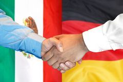 Handshake on Mexico and Germany flag background. Business handshake on the background of two flags. Men handshake on the background of the Mexico and Germany stock photography