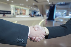 Business handshake with blur background of shopping mall market Royalty Free Stock Photo