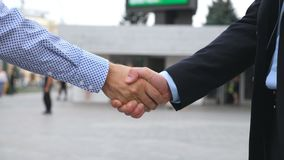 Business handshake with blurred city background. Two businessmen greeting each other in urban environment. Shaking of. Male arms outside. Colleagues meet and stock footage