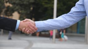 Business handshake with blurred city background. Two businessmen greeting each other in urban environment. Shaking of. Male arms outside. Colleagues meet and stock video footage