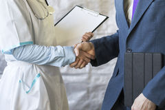 Business handshake. Businessman shaking hands with doctor shaking hands. Royalty Free Stock Photo