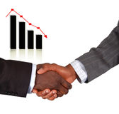 Business handshake with falling graph Stock Photography