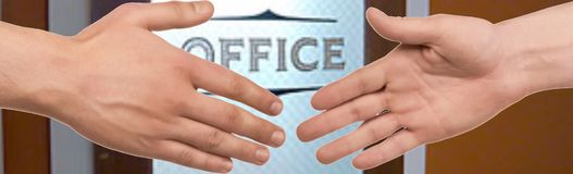Business handshake. Outstretched hands in a handshake in front of door labeled office Royalty Free Stock Photos