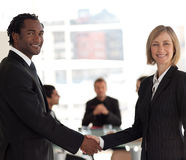 Business handshake in front of workgroup Royalty Free Stock Photos