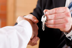 Business Handshake with giving keys Stock Photos