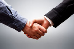 Business handshake. On grey. Concepts of deal, success, contract, cooperation Royalty Free Stock Photos