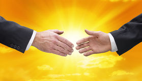 Business Handshake Hands Sky Sun. Two businessmen shaking hands with a yellow sunny sky background Stock Images