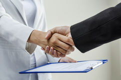 Business handshake. Handshaking after signing contract by businesswomen Stock Photo