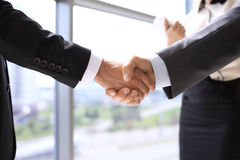 Business handshake at meeting or negotiation in the office. Partners are satisfied because signing contract or financial. Papers Royalty Free Stock Photo