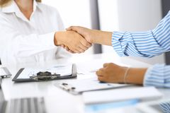 Business handshake at meeting or negotiation in office. Partners shaking hands while satisfied because signing contract. Or financial papers. Best client stock photos