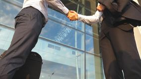 Business handshake outdoor near office building. Two businessmen greeting each other in urban environment. Shaking of. Male arms outside. Colleagues meet and stock video footage