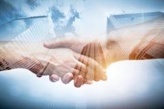 Business handshake over modern skyscrapers, double exposure. stock photos