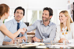 Business handshake. Business people shaking hands on finishing a meeting. Young businesswoman and businessman shaking hands during a meeting. Group of Stock Photo