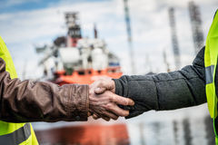 Business handshake in a shipyard. Shipbuilding industry. Shipbuilding deal concluded by a handshake of two engineers. Company contract Stock Image