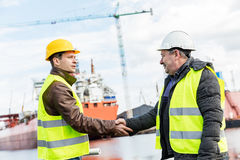Business handshake in a shipyard. Shipbuilding industry. Shipbuilding deal concluded by a handshake of two engineers. Company contract Stock Photos