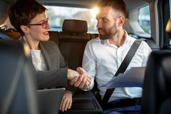 Business handshake to close the agreement in back seat car Stock Photo