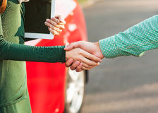 Business handshake to close the deal after buying a car. Between a man and a woman Royalty Free Stock Image