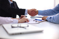 Business handshake. Two businessman shaking hands with each other in the office stock images